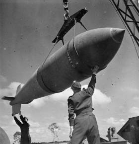 Wikipedia. Royal Air Force Bomber Command, 1942-1945. A 12,000-lb MC deep-penetration bomb (Bomber Command executive codeword 'Tallboy') is hoisted from the bomb dump to its carrier at Woodhall Spa, Lincolnshire, to be loaded into an Avro Lancaster of No. 617 Squadron RAF for a raid on the V-weapon site at Wizernes, France. 617 Squadron were unable to bomb the target on this occasion because of low cloud cover, but were to succeed two days later.